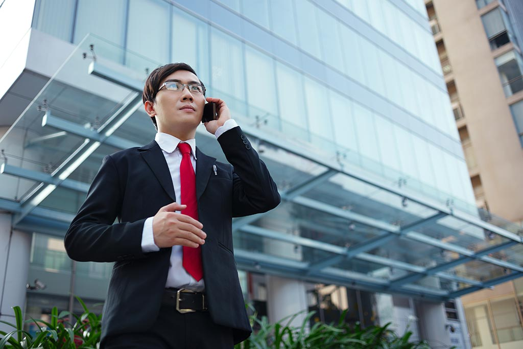 Asian businessman talking on a mobile phone outside office block