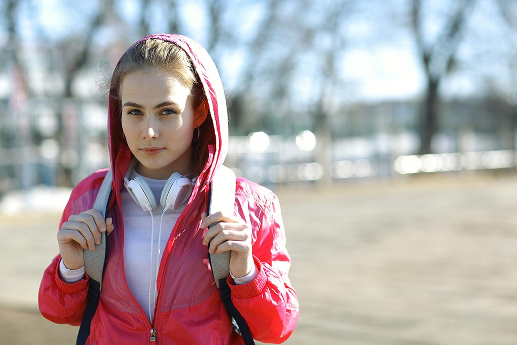 Young lady in a hoodie carrying a backpack